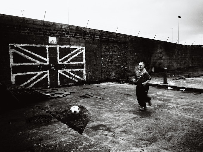 Boy playing football in front of a Union Jack painted on the wall, Shankill (02)