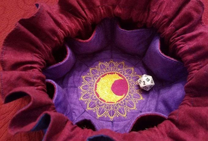 Mollymauk inspired design is stitched on purple with a maroon liner.