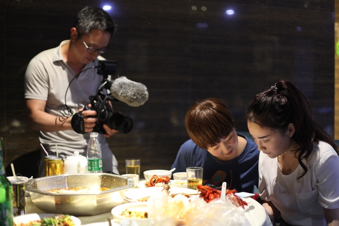 Director Hao Wu films Shen Man dining with a friend