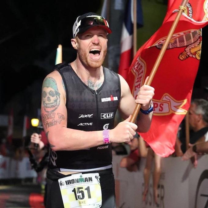 SuperHuman Mike Ergo holding Marine Corp flag