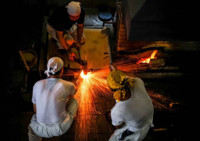 Smiths performing 'orikaeshi-tanren' billet folding at the Bizen Osafune Museum