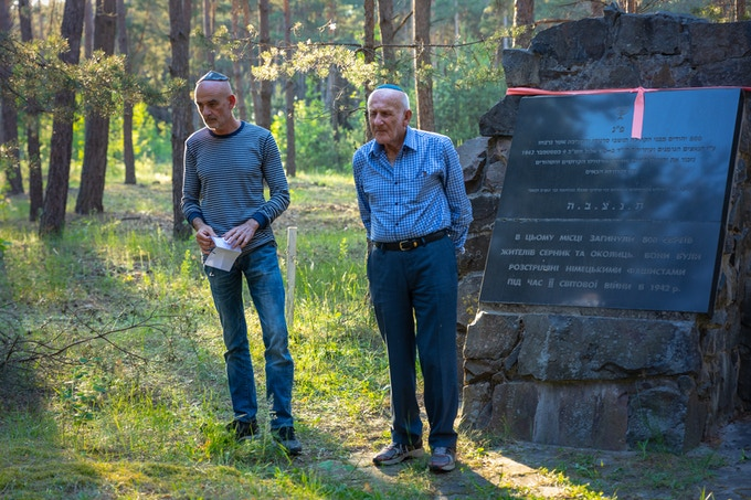 Holocaust survivor Nathan Bobrov and son Dov Bobrov visit mass grave for the first time to say Mourner's Kaddish for family members killed at the site. Serniki, Ukraine. (June 2018) Photo by Anton Skiba.