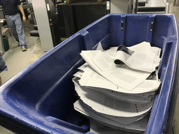Throw-away paper. To calibrate the press, a healthy chunk of the paper is used. This bin fills quickly and its contents are recycled...
