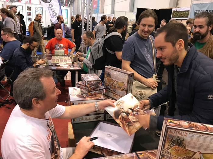 Martin signing copies at Stronghold's booth, Essen Spiel 2018