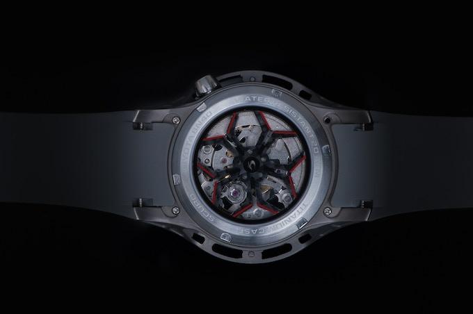 Exhibition sapphire caseback with carbon fiber wheel design insert.