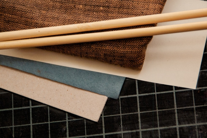 From top: linen cloth, wooden axles, lining paper, exterior paper, binder's board.