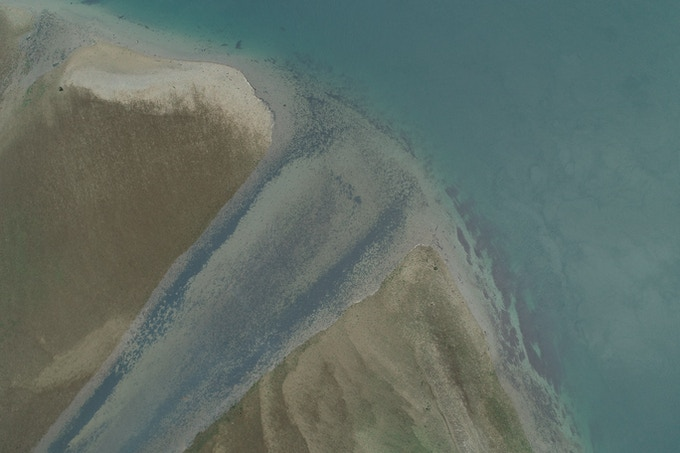 A channel flows through an estuary at low tide. At high tide, this sand is 4m under water.