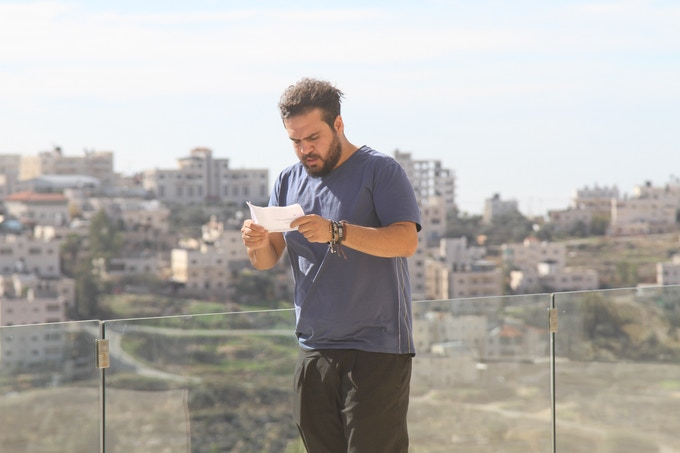 Alaa Shehada studying his lines outside the rehearsal room