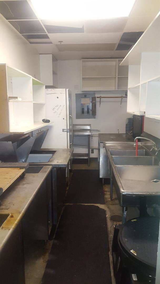 One of the kitchens. Commercial fridge and necessary sinks here. Ceiling tiles need repaired/replaced and thorough cleaning.