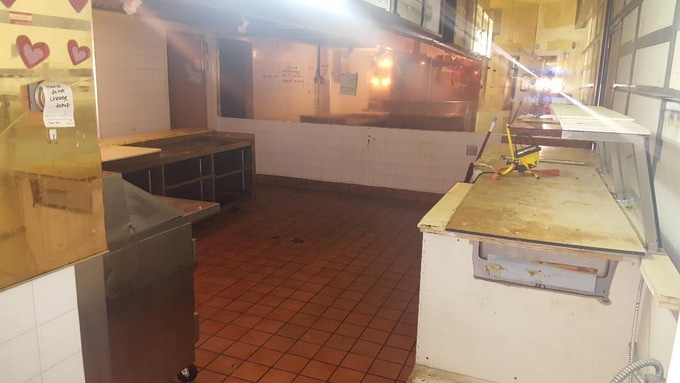 Second kitchen space. They were serving food prepared here. The number of extension cords hanging from the ceiling tiles in this place was amazing. The hood is here. This is also the second store front. May be the best to renovate later into our retail space.