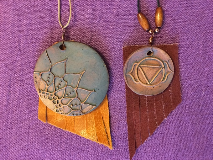 Jaidra's clay process begins with stamps she makes herself; she forms and glazes the amulets before stringing them with semi-precious gems, wood, bone, and leather