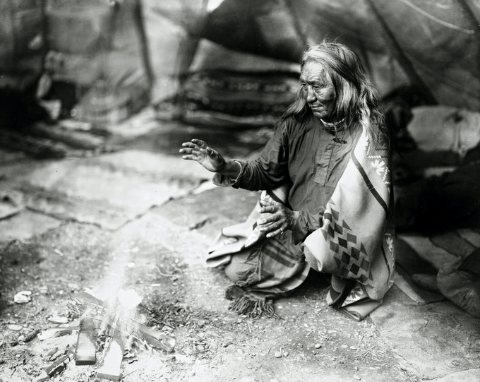 Navajo Indian warming hands over fire in tepee ( 1915 ) - William J. Carpenter/Library of Congress