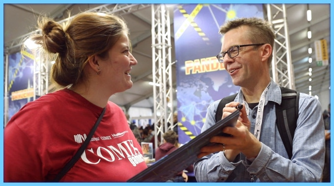 Matt Leacock (Pandemic, Forbidden Sky) signs a game board for a fan at Lucca Comics & Games in Italy.
