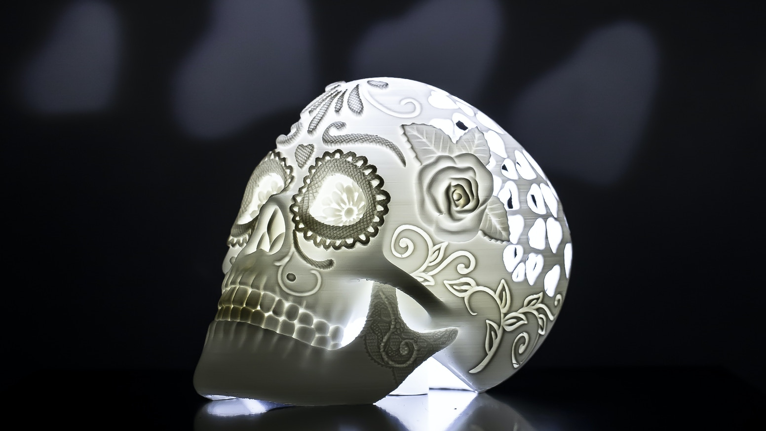 "An illuminated 3D printed ""Day of the Dead"" skull that cast hearts on walls"