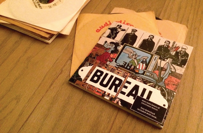 THE BUREAU is an 88-page comic book designed to fit in with your collection of 45rpm 7 inch records. It contains a download for 9 hours of music connected to the comic book story contained within.