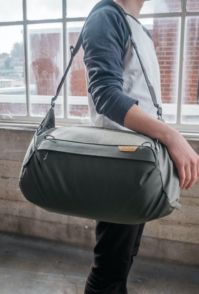 Single-shoulder carry is the most common expected carry style. An adjustable, padded shoulder strap will be included. It will be quickly removable via hook-style quick connectors and stowable inside the bag.
