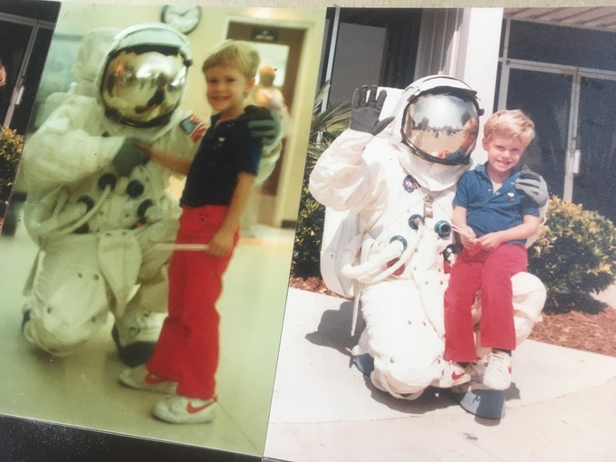 Baby picture, with stylish red pants and an astronaut buddy