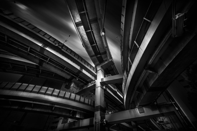 """As well as being a passionate architectural photographer, Yoshihiko is also a professional sound designer in the very demanding video game industry for over 20 years. His sense of sound surely makes his image different from others. Bridges, junctions and modern buildings, these huge structures are his main source of inspirations. In 2016, his panoramic long exposure bridge-city scape """"The Land of Connections"""" have topped on many photo competitions, including one of the prestigious award, International photo award (IPA). He keeps shooting in Japan where he lives for pursuing his urge.   Yoshihiko's philosophy: Shoot ordinary scene, and make it extraordinary."""