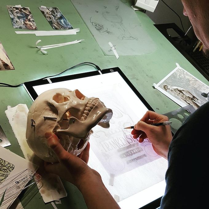 Artist Matt Hughes with his friend Bones creating the cover for Frankenstein Illuminated