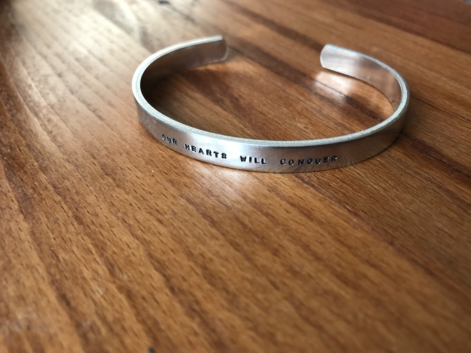 'Our Hearts Will Conquer' hand-pressed aluminium bracelet - available in the 'Bracelet Bundle' Reward!