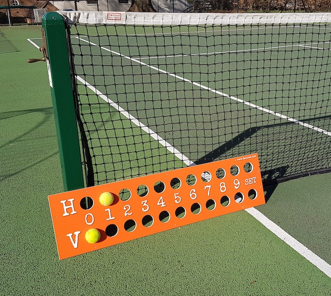 The above photograph is an early prototype.  The actual design has holes to score up to 7 games and 3 sets.  A practical accessory for any player and to any court.