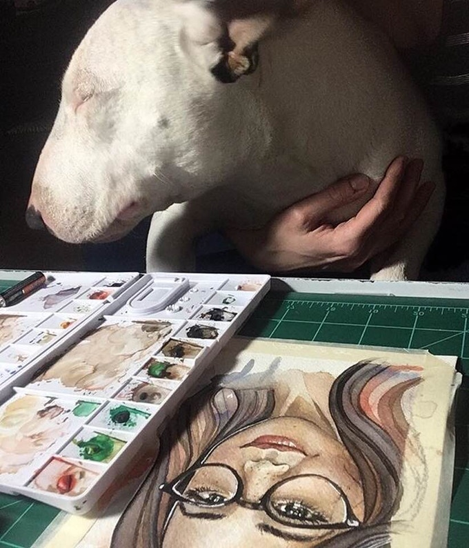 The art of painting while holding an English Bull Terrier.