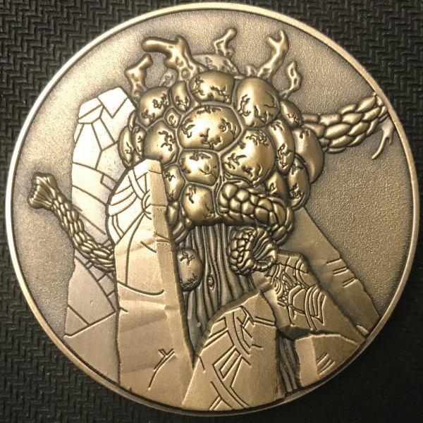 Front of Tcho Tcho coin - plated in antique gold
