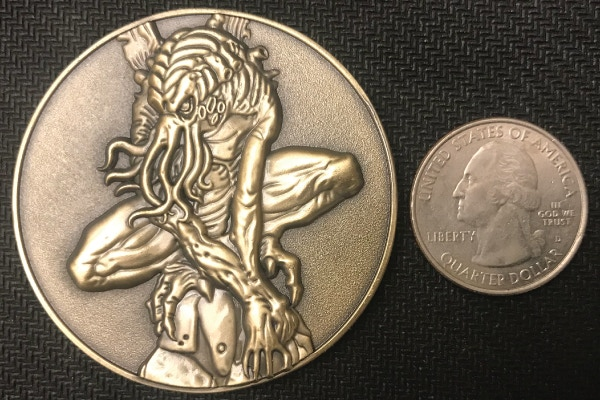 Cthulhu Coin compared in size to US Quarter