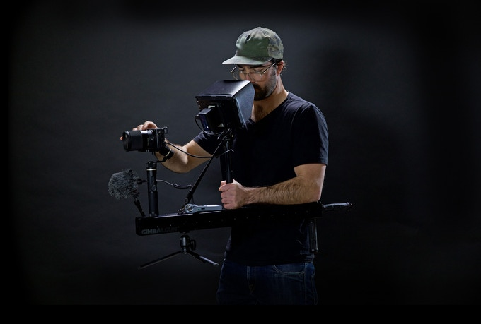 """Shooting from the Hip"" The front weight of the gimbal is supported by the shoulder strap and by my elbow simply resting on the back of the GimbalGun™. This keeps the gimbal at a consistent height. It also allows a free hand to control the camera."