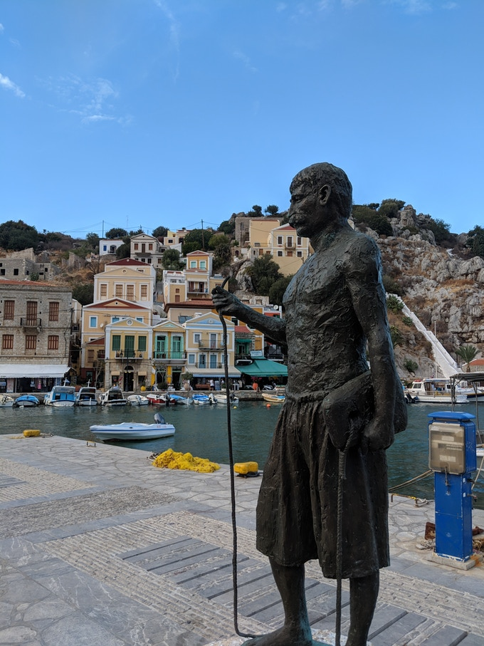 Statue of Stathis Hatzis holding his kampanelopetra stone in Symi
