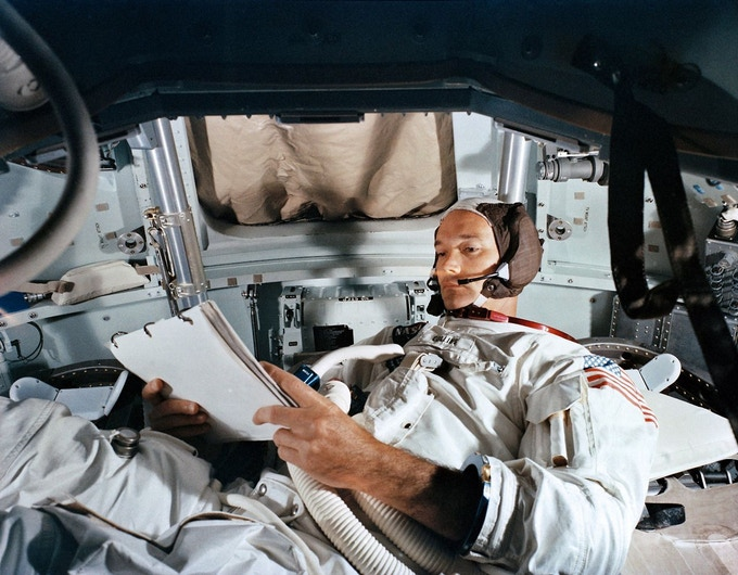 Astronaut Michael Collins studying his copy of the Flight Plan.