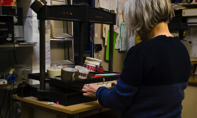 The stitched pages are pressed in a great industrial, iron press.