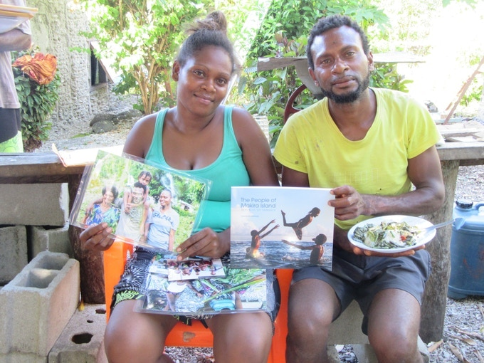 Ruth Jimmy and Robson Billy with their family photos and Makira book.