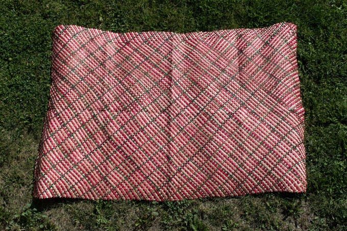 This red and green pandanus mat was woven by Puai Auapa'au. It was made for and donated to this project.