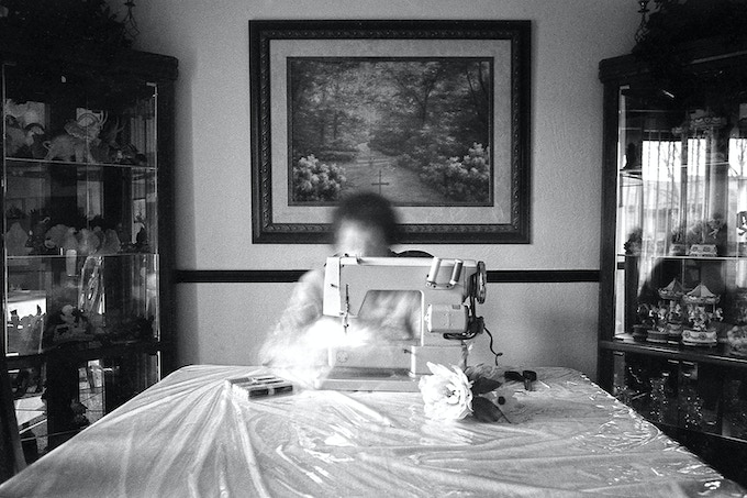 My grandmother sewing at the dinner table. Cedar Rapids, Iowa. 2015