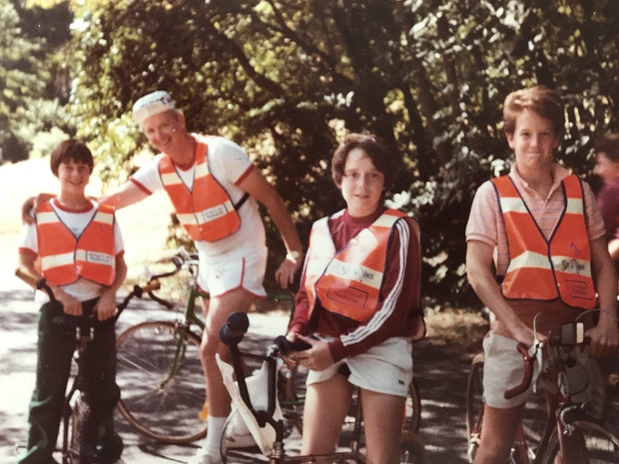 young Dave cycling with family and friends