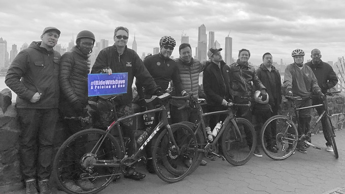 the cast and crew of A Peloton of One beside the NYC skyline