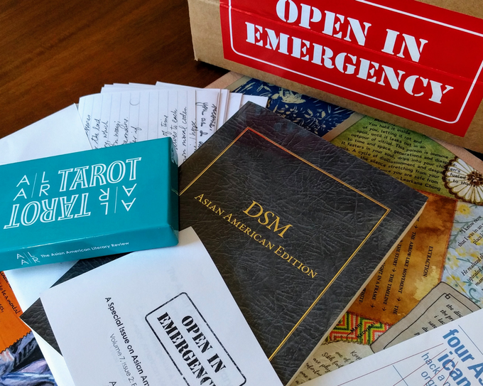 [image description: spread of pieces of original Open in Emergency, with parts of box with red label, DSM cover, tapestry, blue tarot card box, white envelope with letters, pamphlet, and booklet visible]