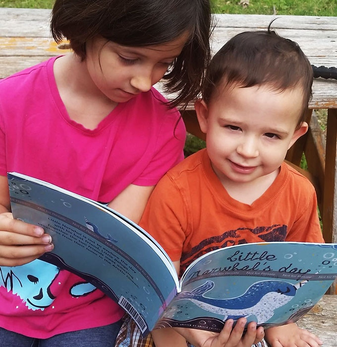 Angela's daughter, Celise, who fought an infection at Dell Children's Hospital, reads a proof copy of Little Narwhal's Day to her little brother.
