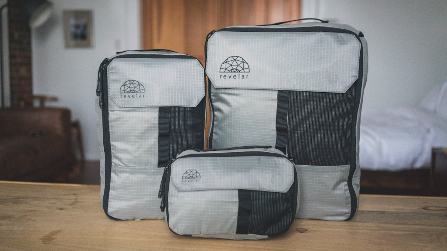 A set of versatile compression packing cubes to maximize space in luggage, while adding multiple carrying options.