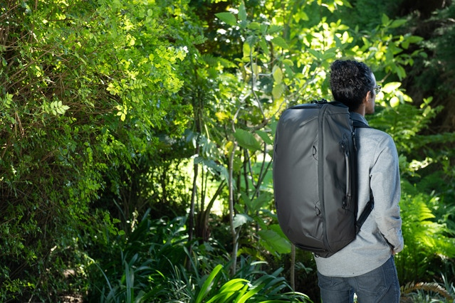 A golden sample of the Travel Duffelpack 65L in black, modeled by Kiran on our design team.
