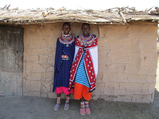 Maasai women pose in front of a manyatta house. Women are usually the ones building the manyatta, for which they source materials in the nearby environment. Joyce Ndugwaya, Amboseli, Kenya.