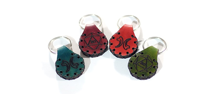 Each keychain is double sided, with our logo and a D20, and come in a variety of colors!