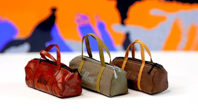 Haute Hero classic duffel bag in 'Cigar' and 'Army Green' colorways; deluxe leather version (on left) in 'saddle tan'. Includes XL Ivy Green shopping bag.
