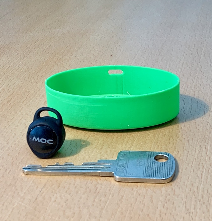 Visual size comparison between a standard house key and prototype box
