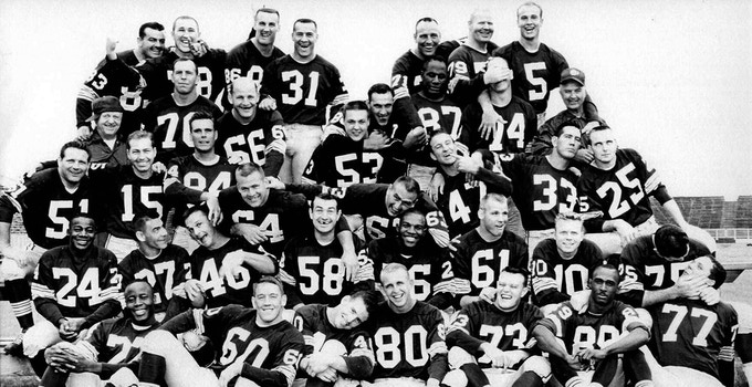 The Green Bay Packers, circa 1962, having a fun moment after taking their official team photo.