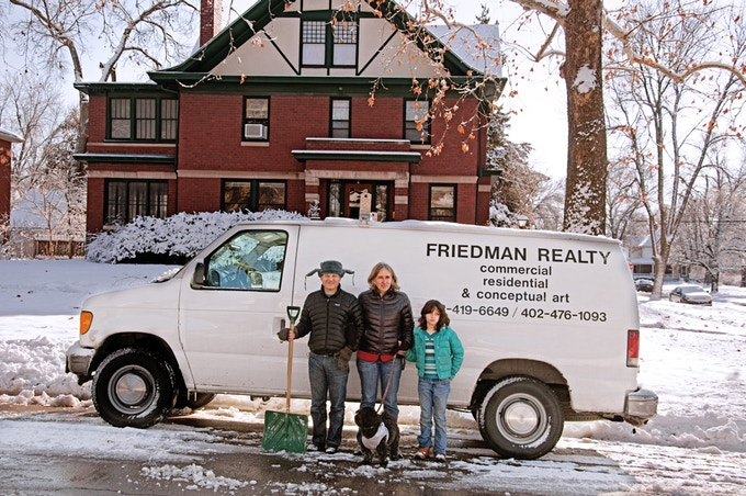 """2013 Archival Digital Print 30"""" x 45"""" This is the van I drive. The text is permantly affixed to truck. This is my family. The composition is based on American Gothic."""