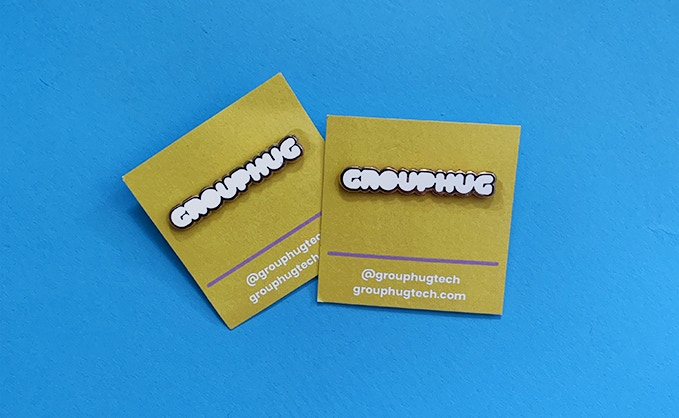 "Grouphug Enamel Pin. Show off your Grouphug love by sporting this white & gold beauty. Dimensions are 2"" long x 0.5"" wide."