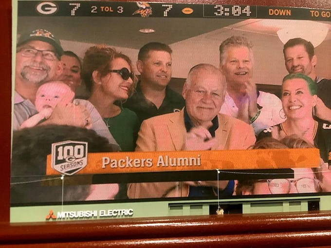 Screenshot of the Kramer family, seated in the Packers' Alumni box the day he was presented his Pro Football Hall of Fame Ring and his name was unveiled in the Packers Ring of Honor. From left: Tony Kramer holding Jack, Stephanie Kramer peeking in, Diana Lee Kramer, Jordan Kramer, Jerry, Daniel Kramer, Alicia Kramer and Matt Kramer.  (The game that day versus the Vikings ended in a 29-29 tie.) Photo credit to Paul Bodi.