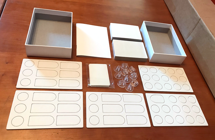 The Vile Invaders BLANK SAMPLE. It's an unprinted version of the whole expansion showing the finish on the box, cards and die-cut pieces. It's missing two plastic zip-bags. See that one little, stubby standee on the page with all the tokens? That's the boat.